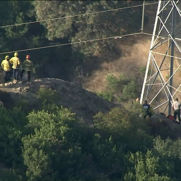 Los Angeles firefighters work to retrieve a body found beneath high-voltage power lines in Griffith Park on Sept. 11, 2019. (Credit: KTLA)