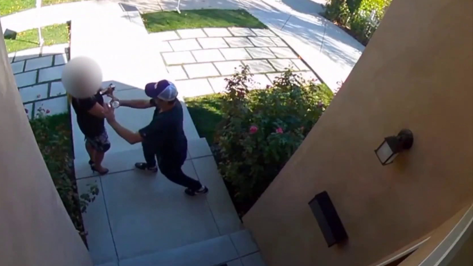 A still from a security video apparently shows a man shoving a real estate agent during an open house in Encino on Sept. 22, 2019.