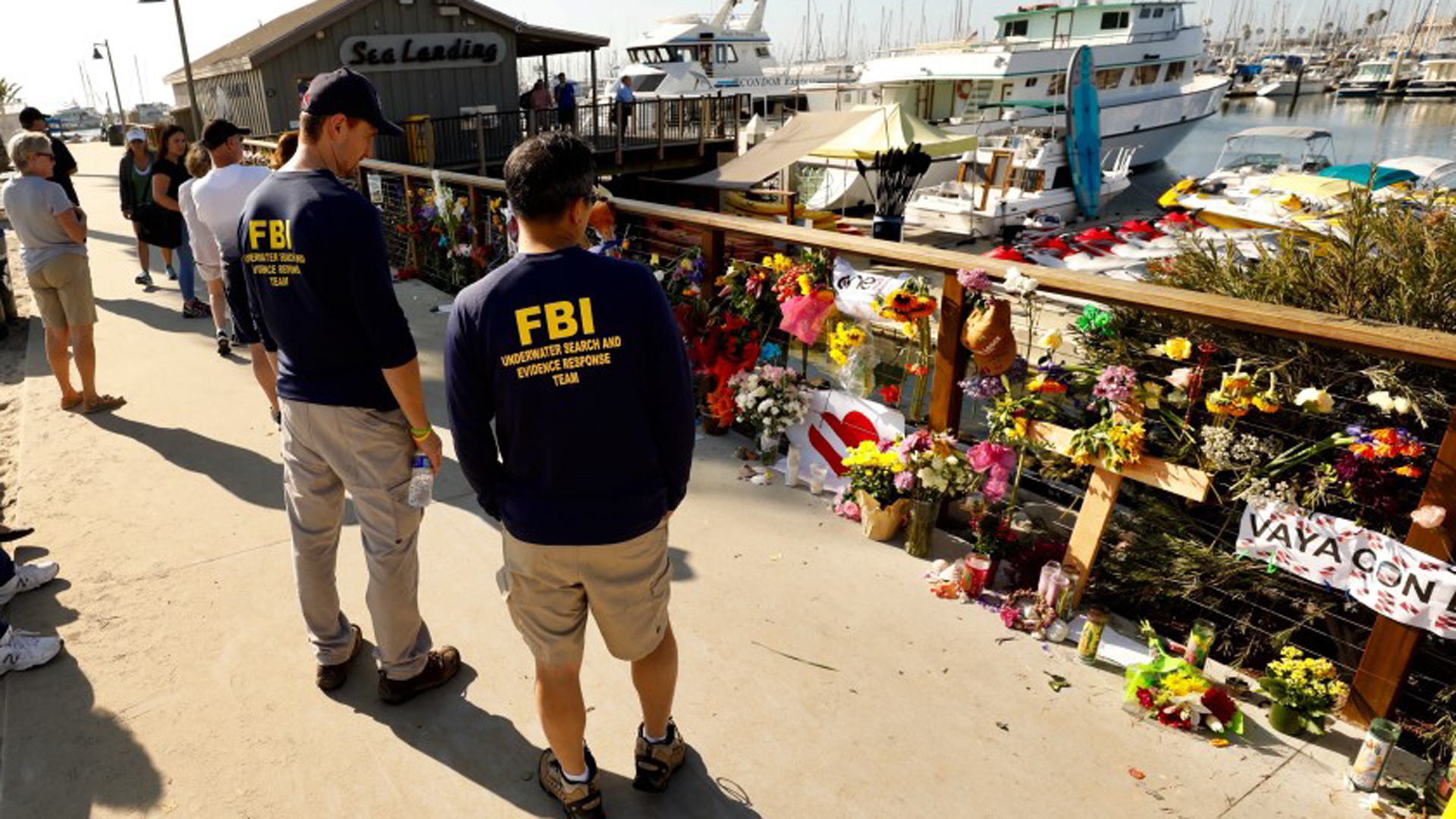 Members of an FBI dive team look at a growing memorial to the victims of the Labor Day fire aboard the Conception, a dive boat that was anchored off Santa Cruz Island. (Al Seib/Los Angeles Times)