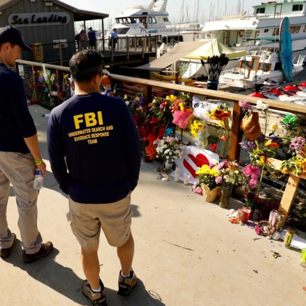 Members of an FBI dive team look at a growing memorial to the victims of the Labor Day fire aboard the Conception, a dive boat that was anchored off Santa Cruz Island. (Credit: Al Seib/Los Angeles Times)