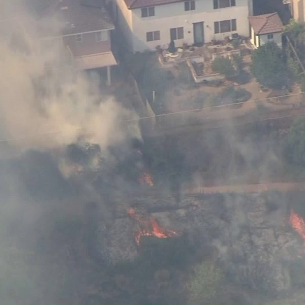 Firefighters beat back flames as they burned dangerously close to homes in Murrieta on Sept. 5, 2019. (Credit: KTLA)