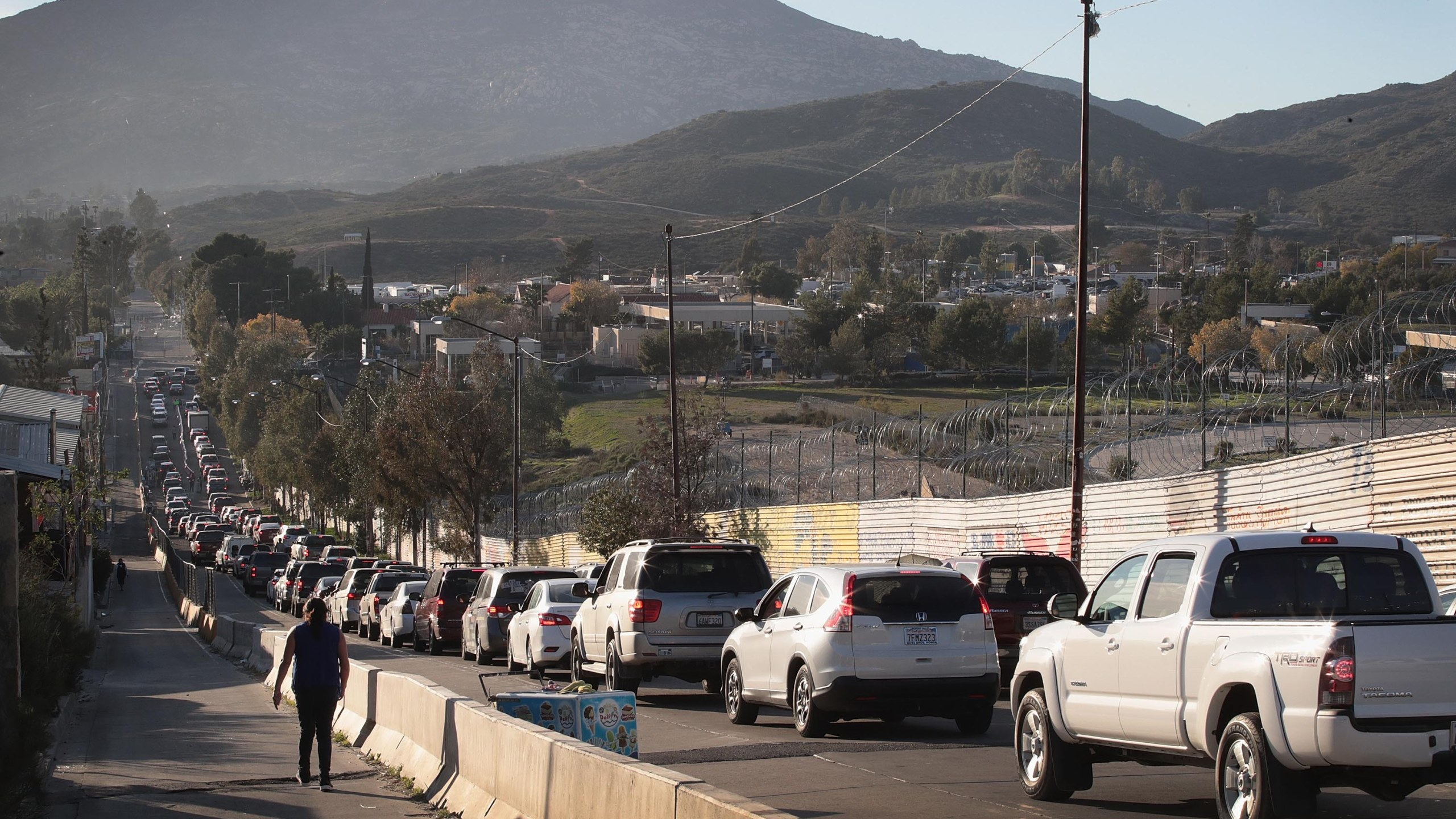 Motorists heading to the United States from Tecate, Mexico, wait along the U.S. border wall to pass through the port of entry on Jan. 27, 2019. (Credit: Scott Olson / Getty Images)