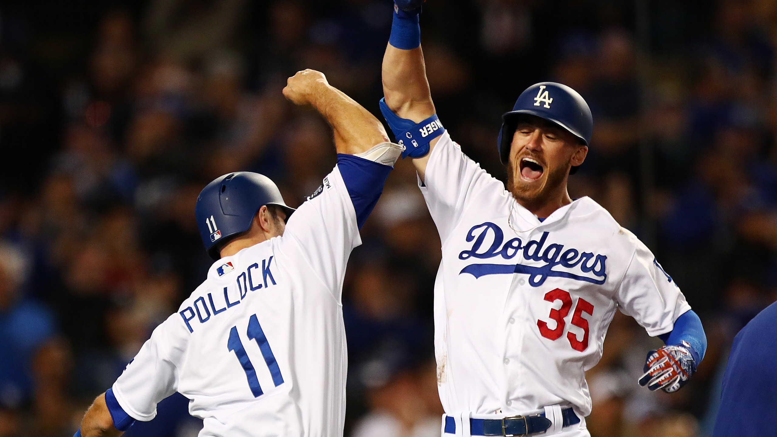 Cody Bellinger #35 of the Los Angeles Dodgers celebrates with A.J. Pollock #11 after hitting a grand slam against the San Francisco Giants during the third inning at Dodger Stadium on April 2, 2019. (Credit: Yong Teck Lim/Getty Images)