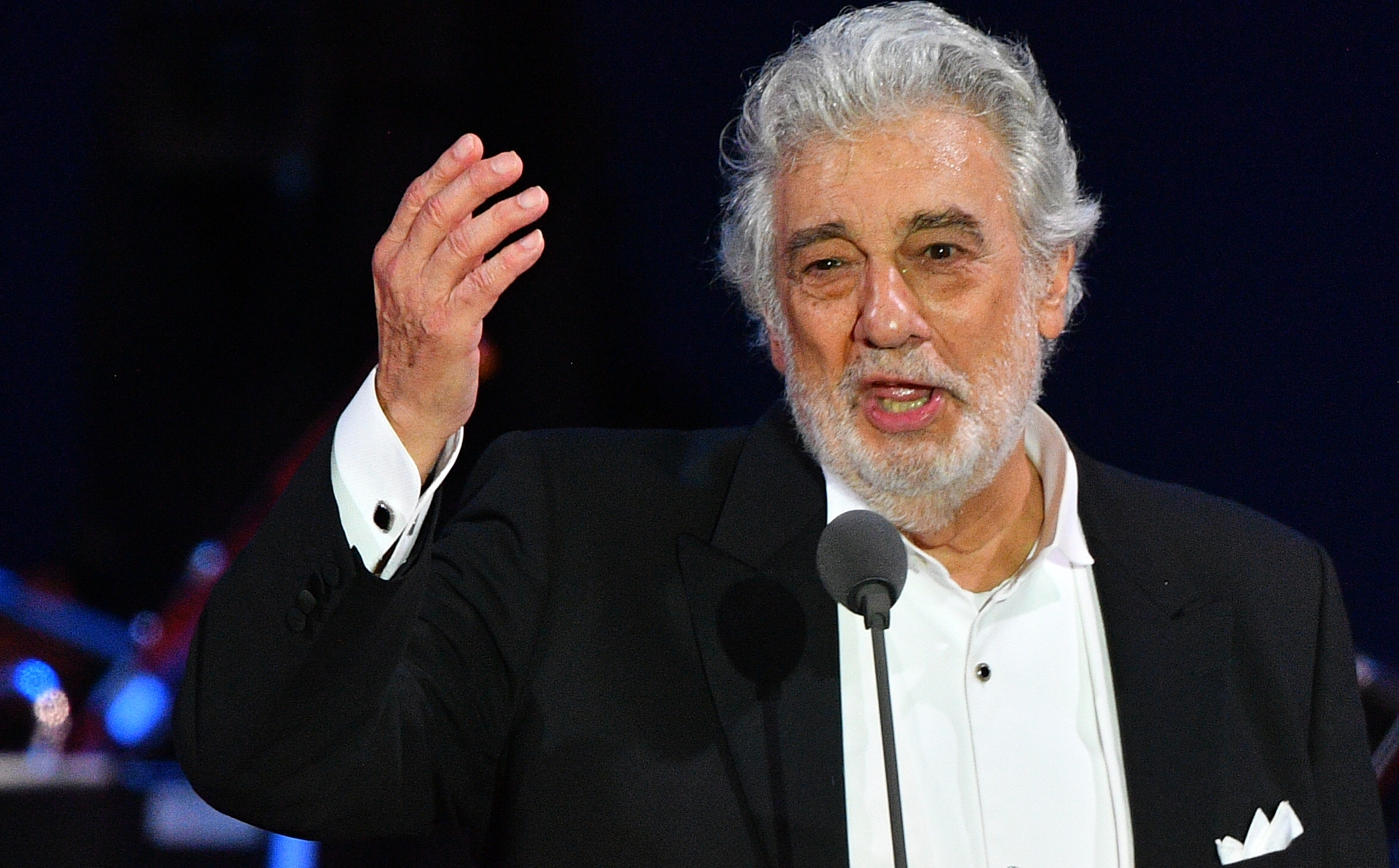 Spanish tenor Placido Domingo gestures as he performs during his concert in the newly inaugurated sports and culture centre 'St Gellert Forum' in Szeged, southern Hungary, on Aug. 28, 2019. (Credit: ATTILA KISBENEDEK/AFP/Getty Images)