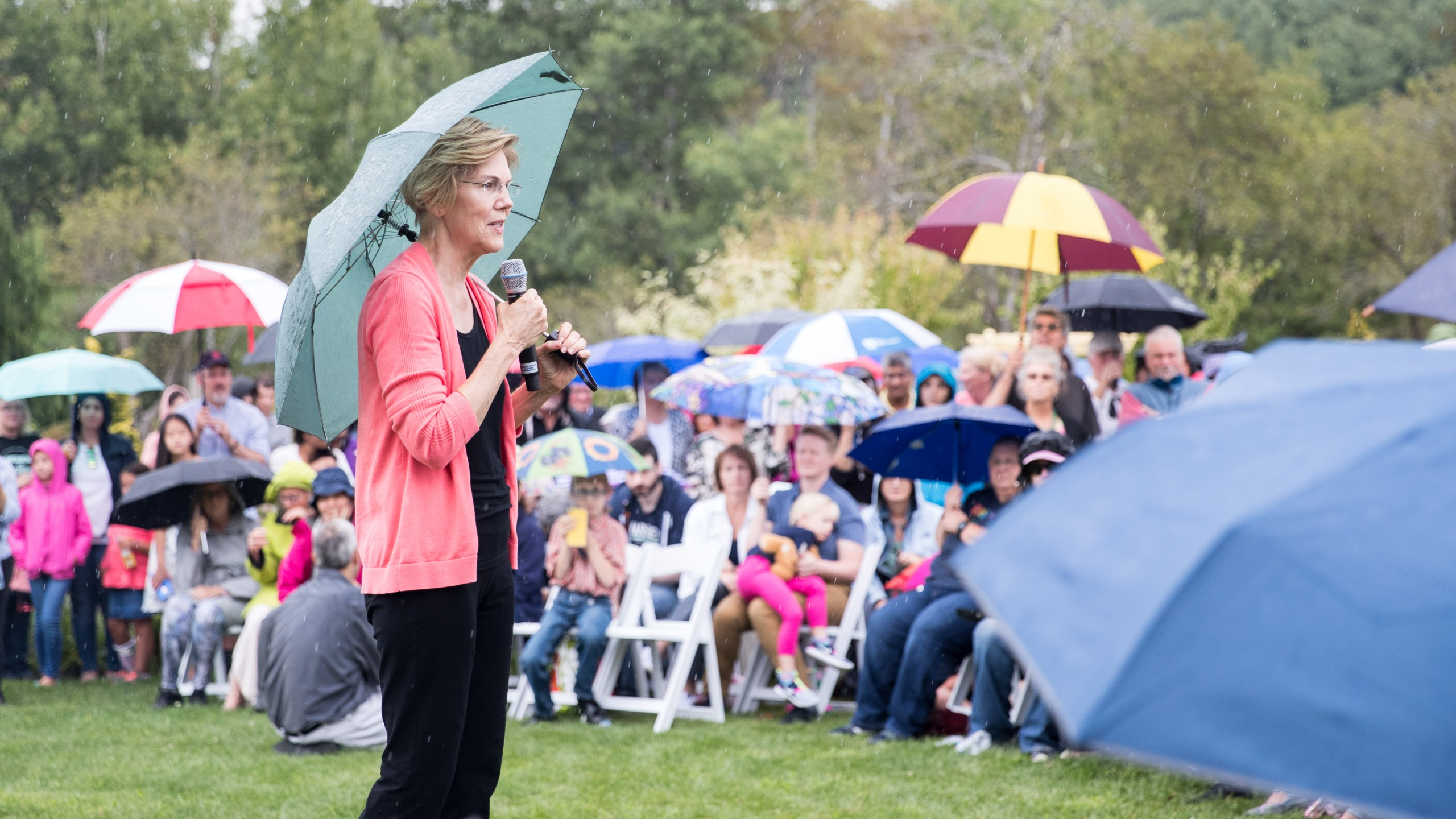 Sen. Elizabeth Warren speaks to a crowd of around 800 as it begins to rain during a Labor Day house party in Hampton Falls, New Hampshire, on Sept. 2, 2019. (Credit: Scott Eisen / Getty Images)