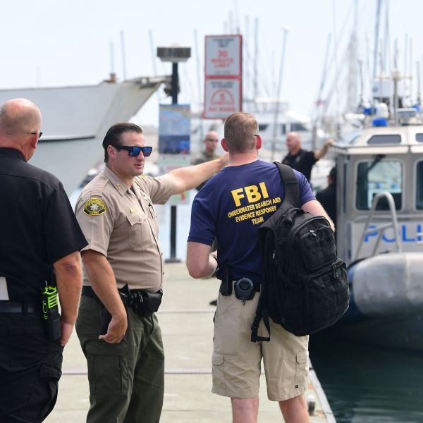 Law enforcement personnel, including a member of the FBI Underwater Search and Evidence Response Team, wait on a jetty on Sept. 3, 2019, in Santa Barbara. (Credit: FREDERIC J. BROWN/AFP/Getty Images)