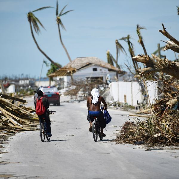 Residents pass damage caused by Hurricane Dorian on September 5, 2019, in Marsh Harbour, Great Abaco Island in the Bahamas. (Credit: BRENDAN SMIALOWSKI/AFP/Getty Images)