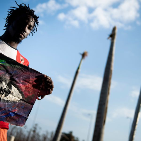 "Shaquille Joseph poses with a painting that he made of the eye of Hurricane Dorian while waiting at Marsh Harbor International Airport for evacuation after Hurricane Dorian Sept. 7, 2019, in Marsh Harbor, Great Abaco. - He made the painting of the eye because he was able to escape flood waters and get to his roof during the stillness of the hurricane's eye. Bahamians who lost everything in the devastating passage of Hurricane Dorian were scrambling that same day to escape the worst-hit islands by sea or by air, after the historically powerful storm left at least 43 people dead with officials fearing a ""significantly"" higher toll. (Credit: BRENDAN SMIALOWSKI/AFP/Getty Images)"