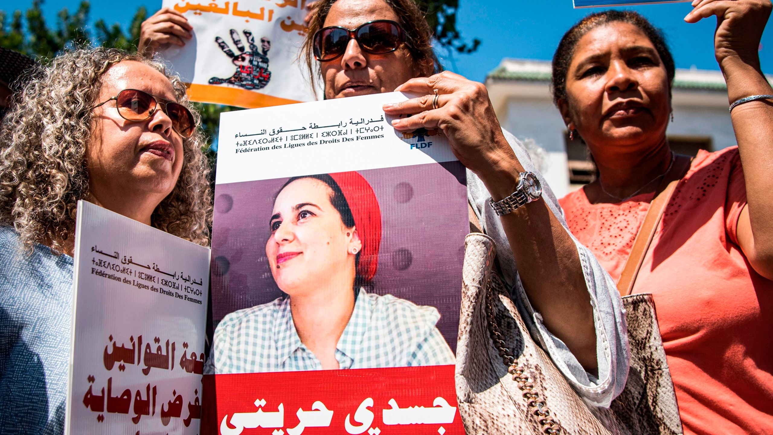 "Demonstrators hold up a sign showing the portrait of Hajar Raissouni, a Morrocan journalist of the daily newspaper Akhbar El-Youm, with a caption below in Arabic reading ""My body, My freedom"", as they gather outside a courthouse holding her trial on charges of abortion in the capital Rabat on Sept. 9, 2019. (Credit: FADEL SENNA/AFP/Getty Images)"