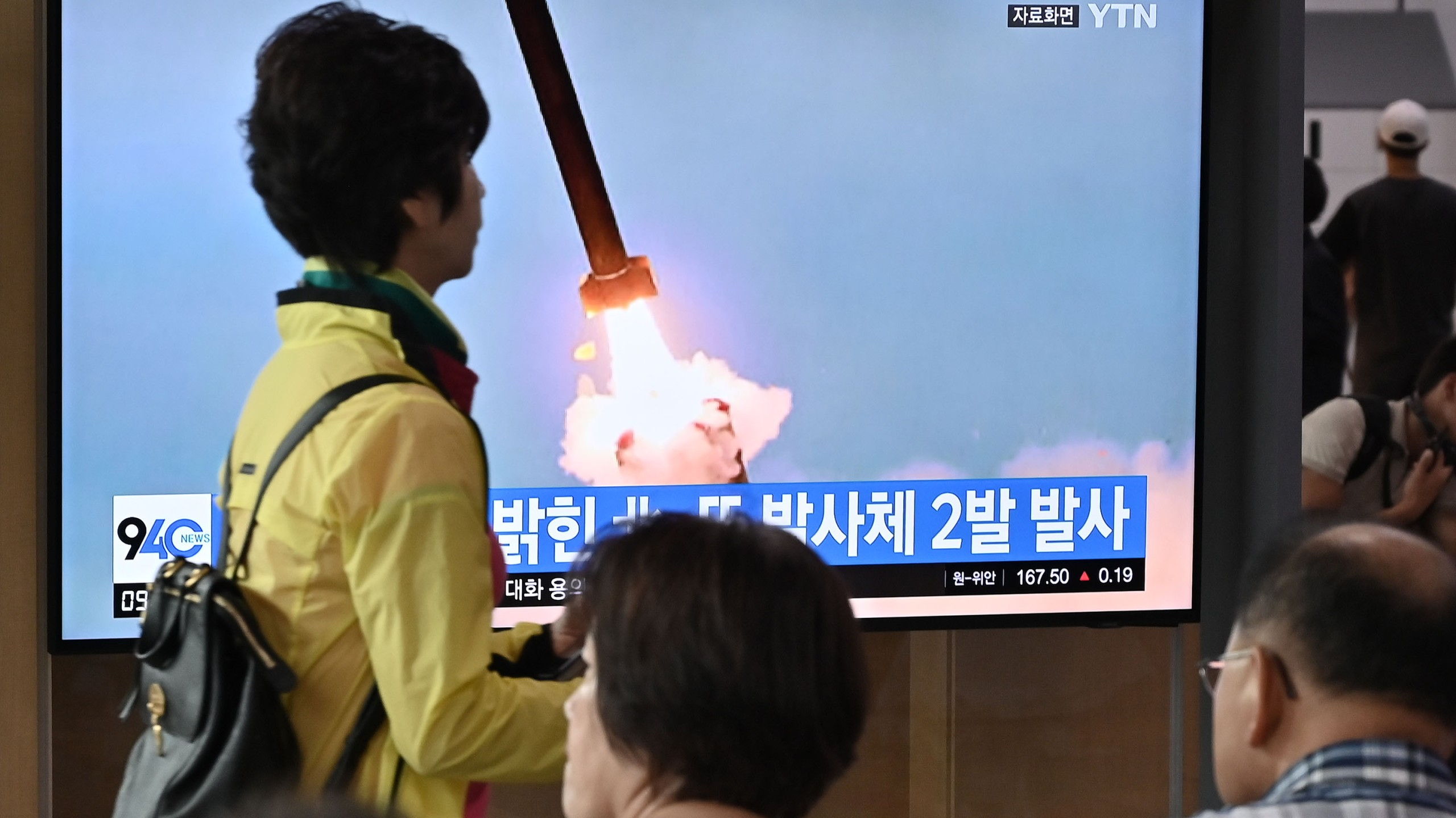 People watch a television news screen showing file footage of a North Korean missile launch, at a railway station in Seoul on September 10, 2019. (Credit: JUNG YEON-JE/AFP/Getty Images)