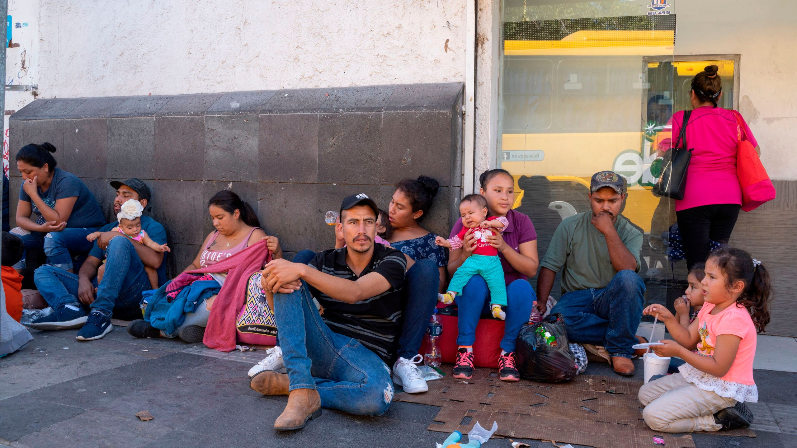 Migrants, mostly from Mexico, are pictured sitting on the ground waiting near the Paso del Norte Bridge at the Mexico-US border, in Ciudad Juarez, Mexico, on September 12, 2019. (Credit: PAUL RATJE/AFP/Getty Images)