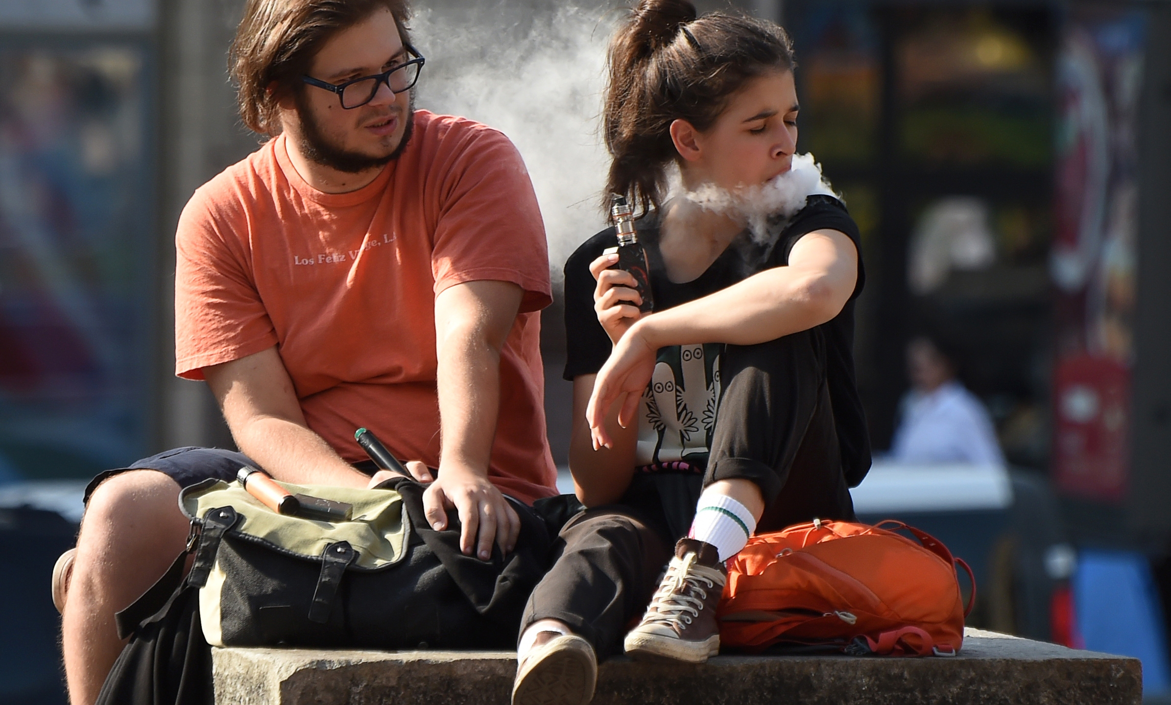 A couple smokes electronic cigarettes (e-cigarettes) in central Kiev on a warm autumn day on Sept. 13, 2019. (Credit: Sergei SUPINSKY/AFP/Getty Images)