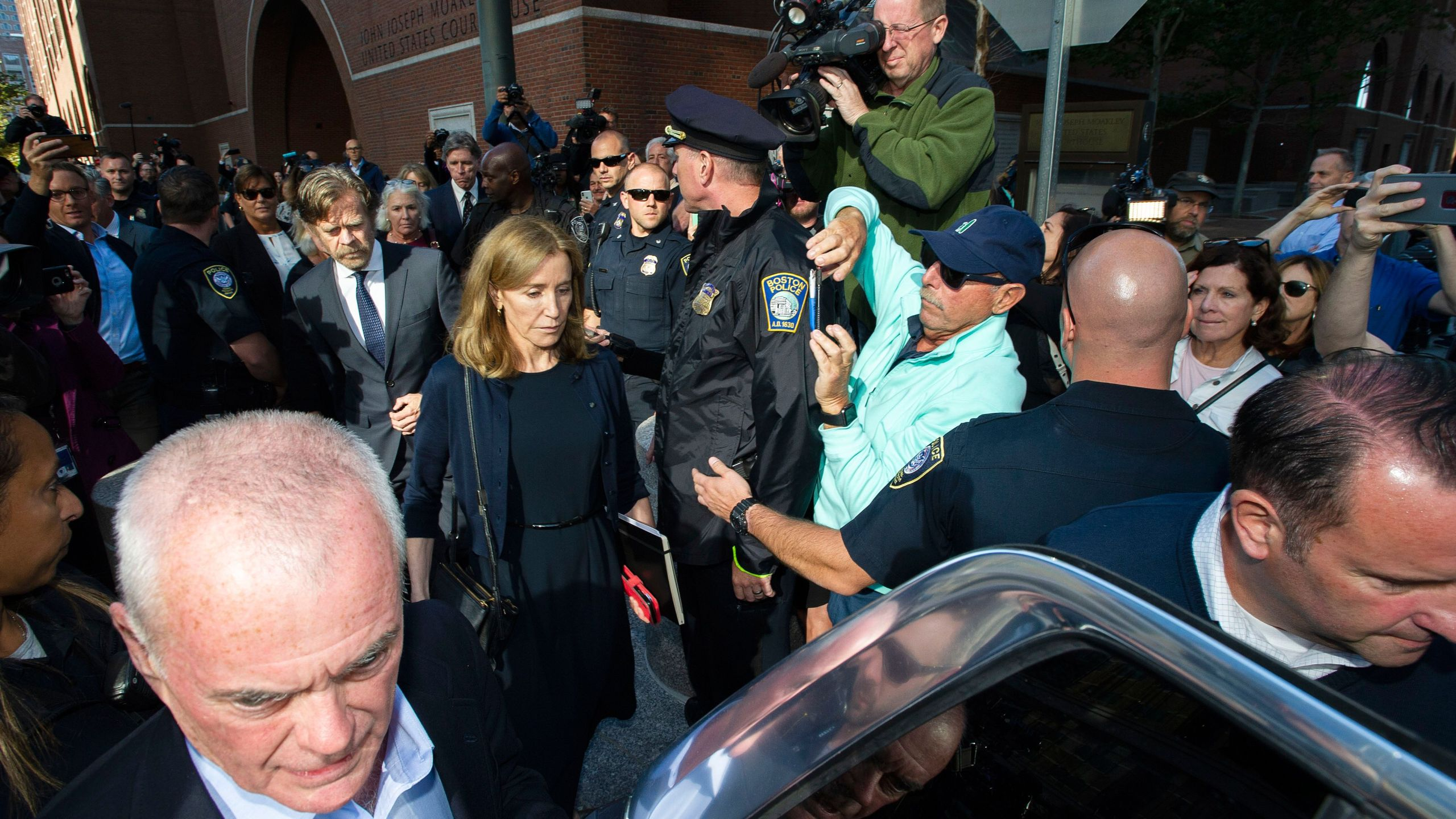 Felicity Huffman, escorted by her husband William H. Macy, leaves the John Joseph Moakley U.S. Courthouse in Boston, where she was sentenced for her role in the college admissions scandal, on Sept. 13, 2019. (Credit: JOSEPH PREZIOSO/AFP/Getty Images)