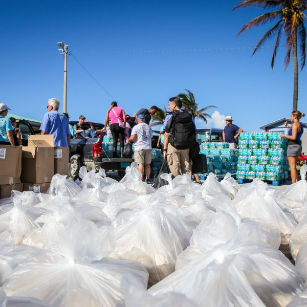 People from the Bahamas Relief Cruise, operated by the Bahamas Paradise Cruise Line, stand next to some 20,000 meals prepared for Bahamians to be delivered to distribution centers and homes in the aftermath of Hurricane Dorian and Tropical Storm Humberto in Freeport, Grand Bahama, Bahamas, on Sept. 17, 2019. (Credit: ZAK BENNETT/AFP/Getty Images)
