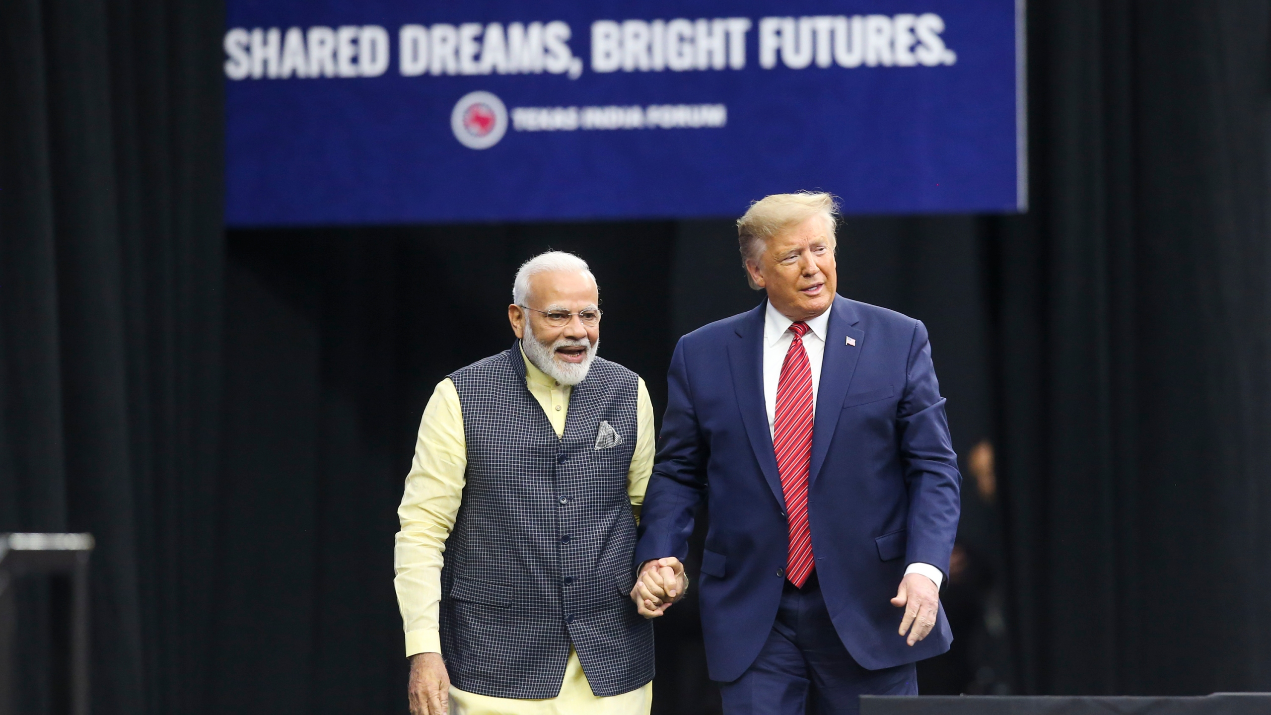 India Prime Minister Narendra Modi and President Donald Trump hold hands at the Community Summit on Sept. 22, 2019, at NRG Stadium in Houston, Texas. (Credit: Thomas B. Shea/AFP/Getty Images)