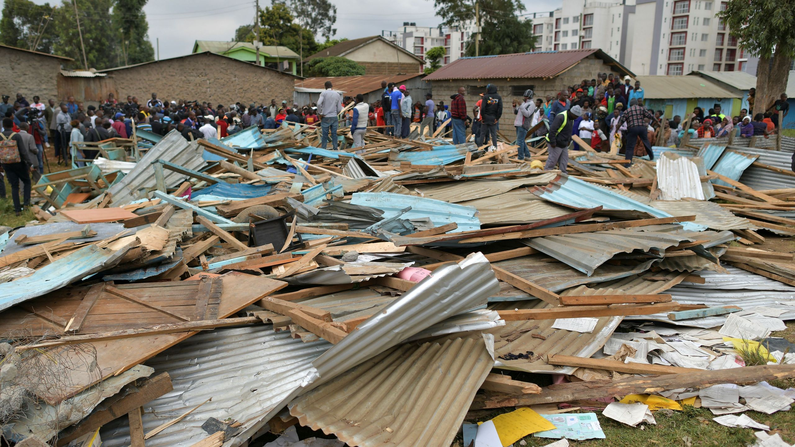 Relatives stand on debris of a collapsed school building, on September 23, 2019 in Nairobi. (Credit: TONY KARUMBA/AFP/Getty Images)