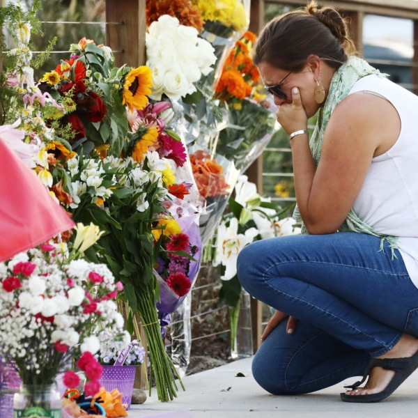 A woman looks emotional as she kneels at a makeshift memorial in Santa Barbara Harbor for victims of the Conception boat fire on Sept. 3, 2019, in Santa Barbara. (Credit: Mario Tama/Getty Images)