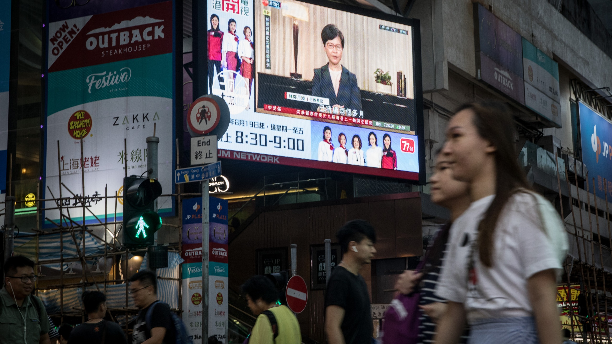 People walk past a big screen replaying Hong Kong Chief Executive Carrie Lam announcing the formal withdrawal of the extradition bill on September 04, 2019 in Hong Kong, China. (Credit: Chris McGrath/Getty Images)