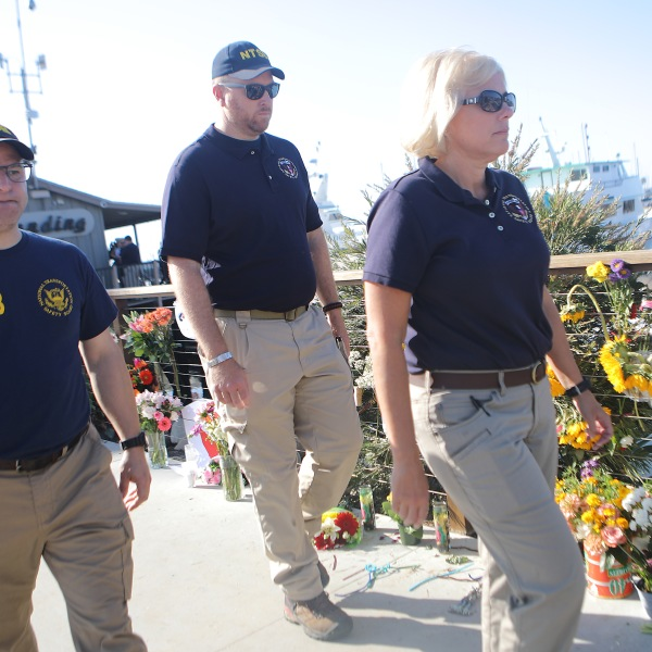 National Transportation Safety Board member Jennifer Homendy, at right, walks with other NTSB officials past a makeshift memorial for victims of the Conception boat fire in Santa Barbara on Sept. 4, 2019. (Credit: Mario Tama / Getty Images)