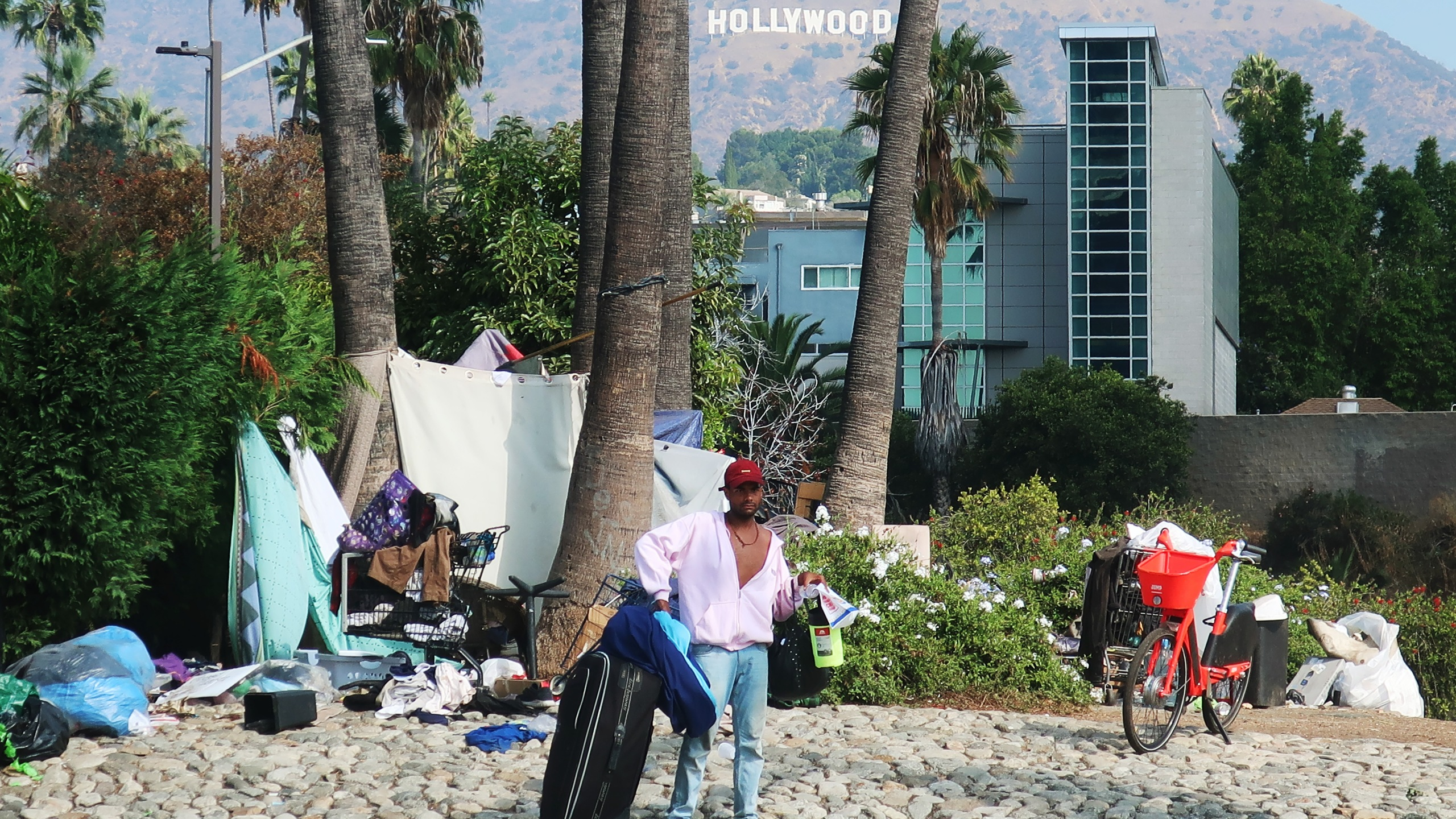 A man stands in front of a homeless encampment, with the Hollywood sign in the background, on Sept. 23, 2019. (Credit: Mario Tama / Getty Images)