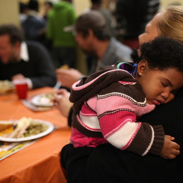 Eight month-old Canziz Lynch sleeps as people enjoy a free Thanksgiving meal at CityTeam Ministries on Nov. 23, 2011, in San Francisco. CityTeam Ministries in San Francisco fed nearly 400 Thanksgiving meals to homeless and underprivileged people that year. (Credit:Justin Sullivan/Getty Images)