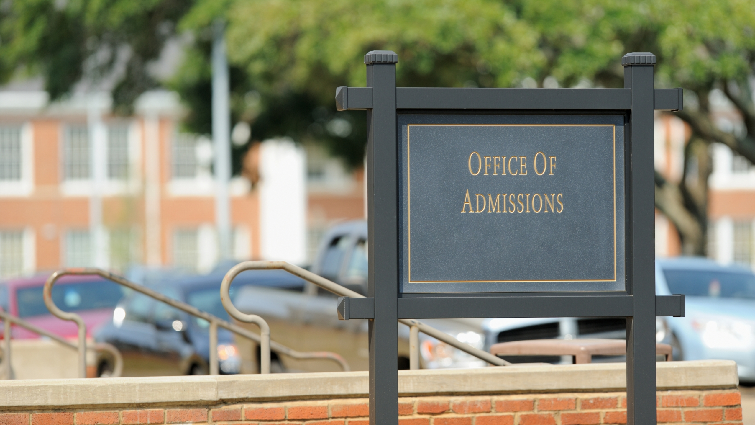 An office of admission sign is seen on a university campus. (Credit: iStock / Getty Images Plus)