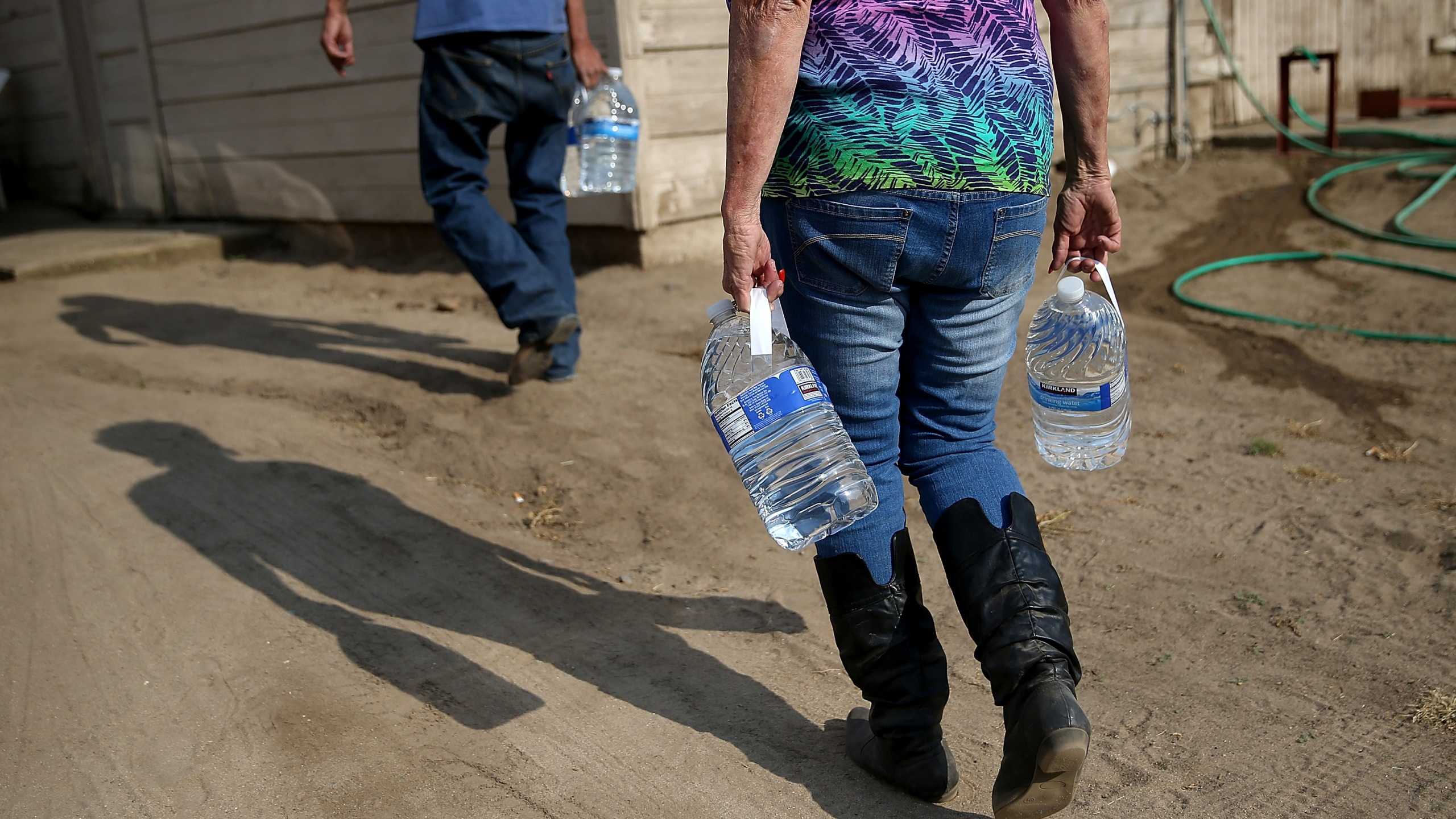 Donna Johnson (R) delivers drinking water to a resident who has no running water on April 23, 2015, in Porterville, Calif. (Credit: Justin Sullivan/Getty Images)