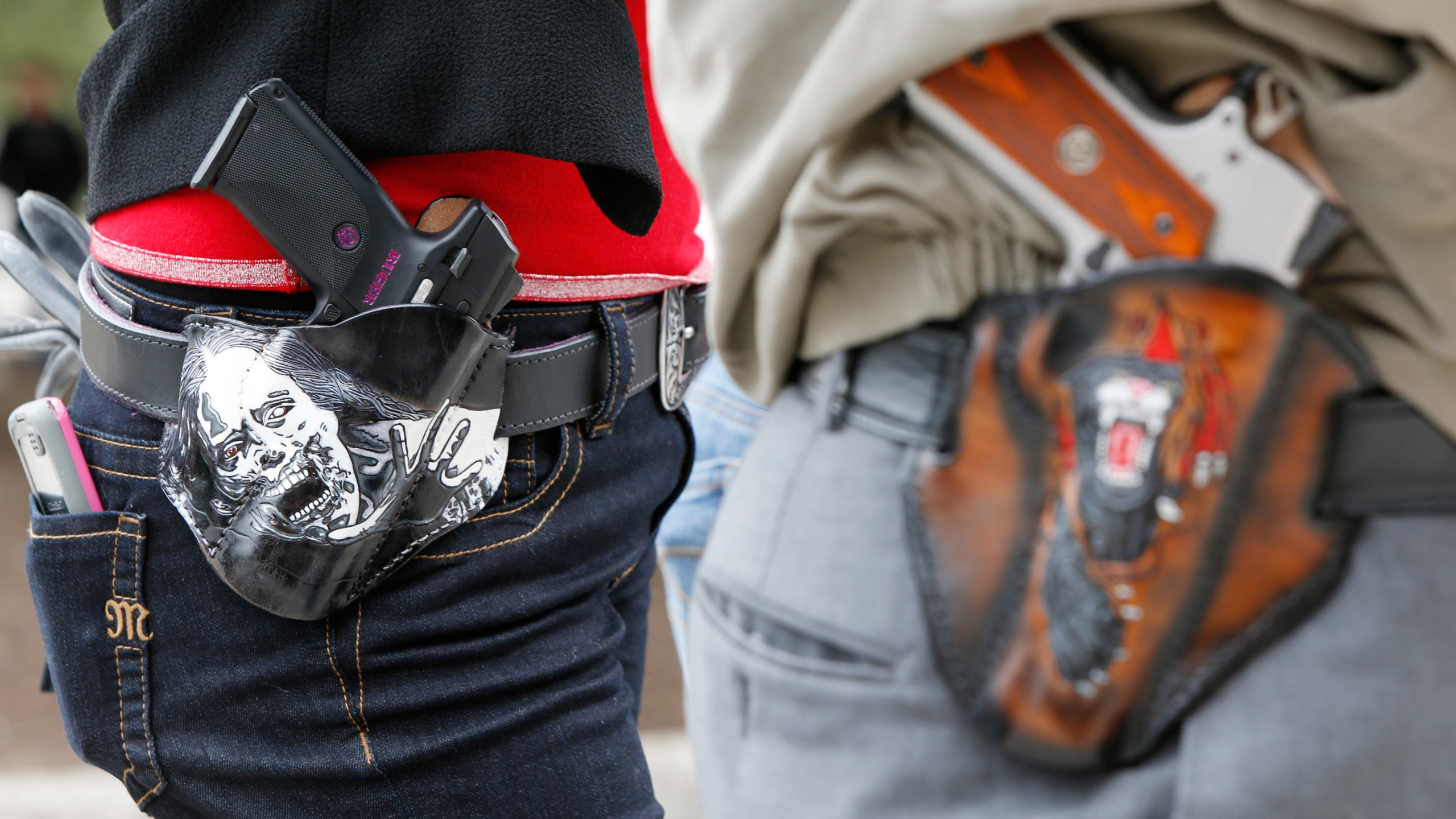 Art and Diana Ramirez of Austin with their pistols in custom-made holsters during an open-carry rally at the Texas State Capitol on Jan. 1, 2016 in Austin, Texas. (Credit: Erich Schlegel/Getty Images)
