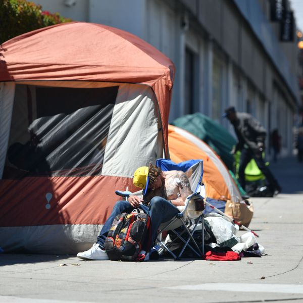 A homeless man sleeps in front of his tent along Van Ness Avenue in downtown San Francisco on June, 27, 2016. (Credit: JOSH EDELSON/AFP/Getty Images)