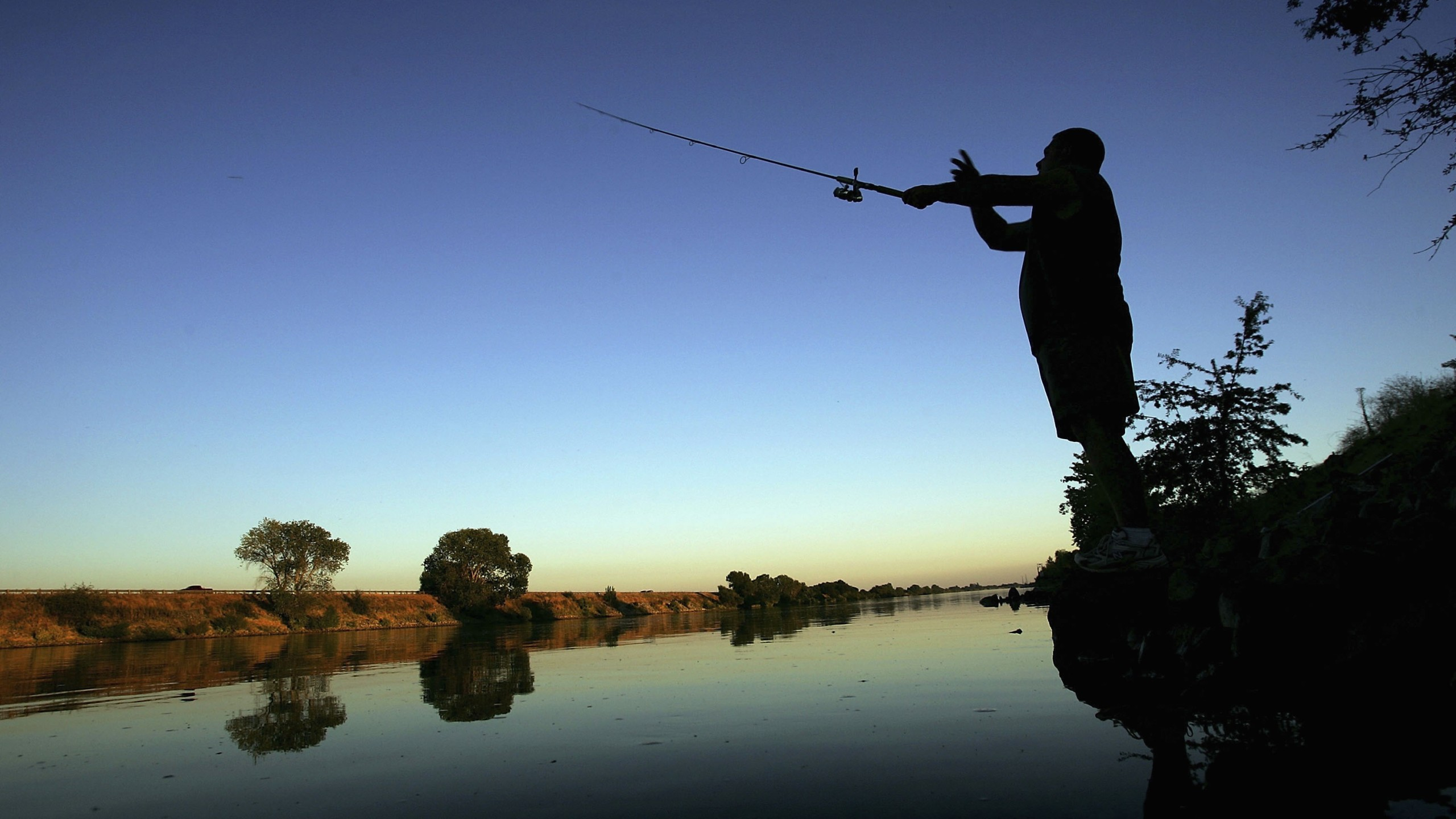 A fisherman casts his line into the Sacramento River in the Sacramento-San Joaquin River Delta on September 29, 2005 south of Sacramento, California. (Credit: David McNew/Getty Images)