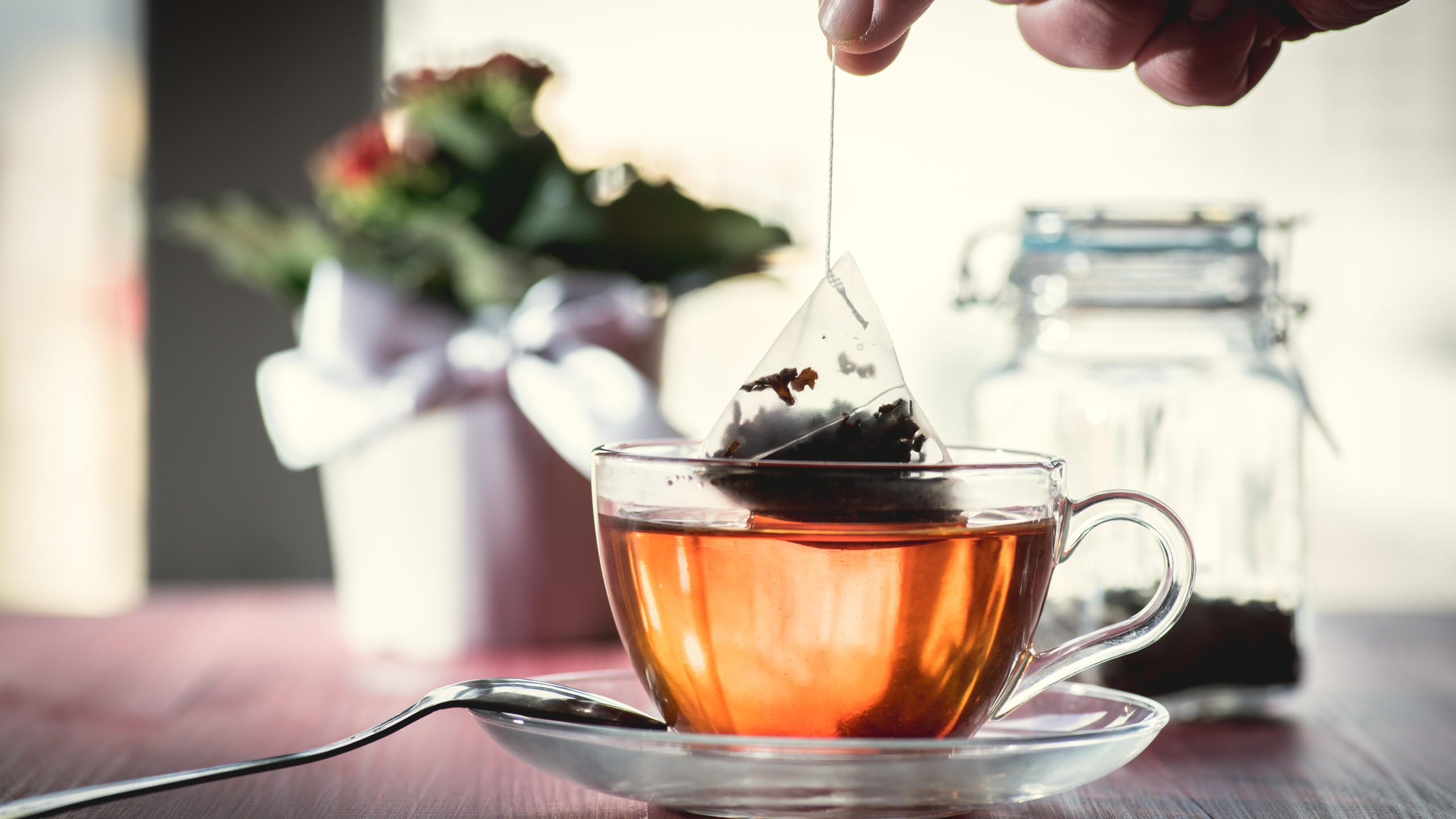 A stock photo shows someone putting a tea bag into hot water. (Credit: Stock / Getty Images Plus)