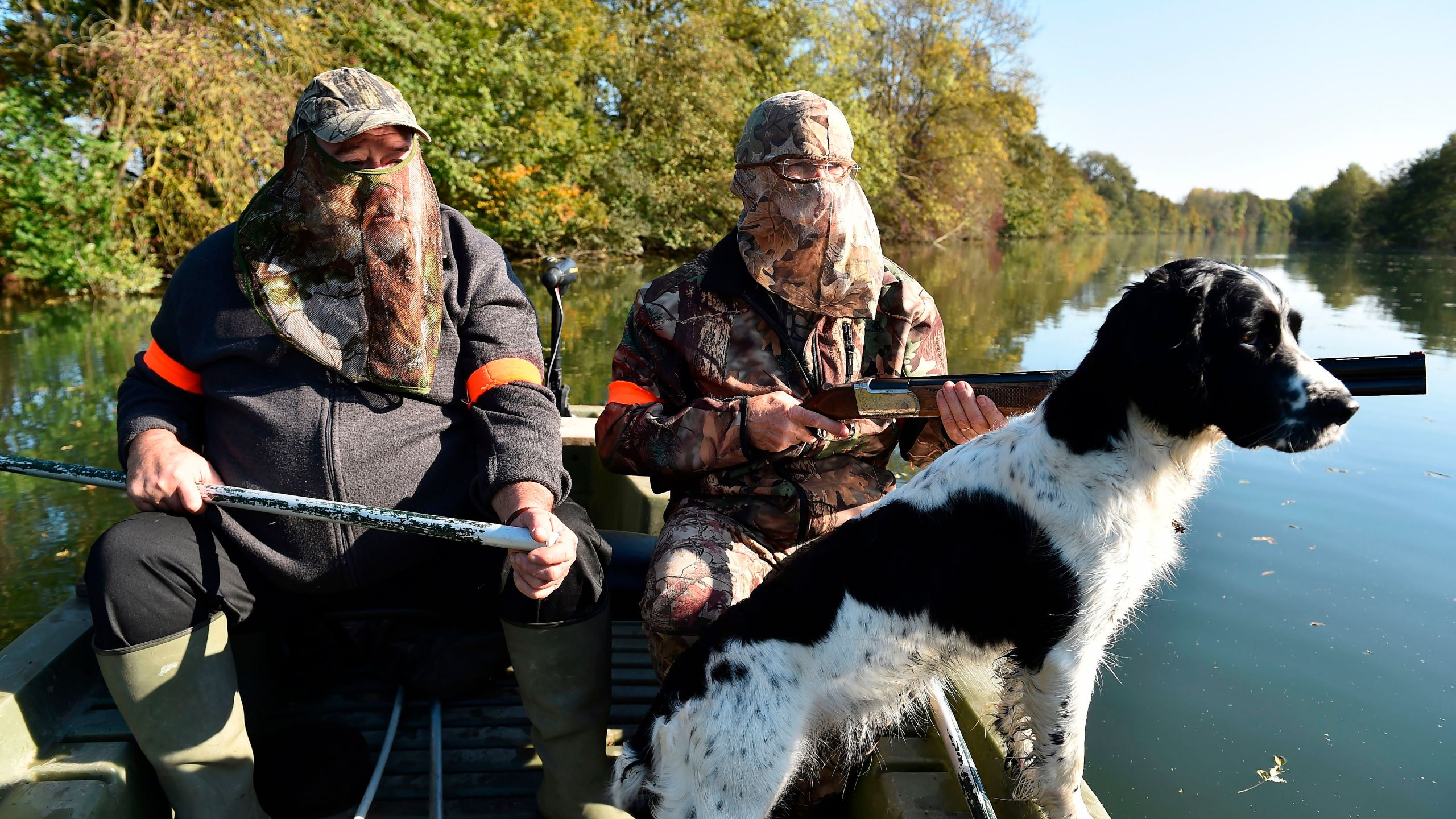 Waterfowl hunters with their Springer Spaniel dog, steer a boat on Le Loir river, during a duck hunting in Vaas, France, on Oct. 15, 2017. (Credit: JEAN-FRANCOIS MONIER/AFP/Getty Images)