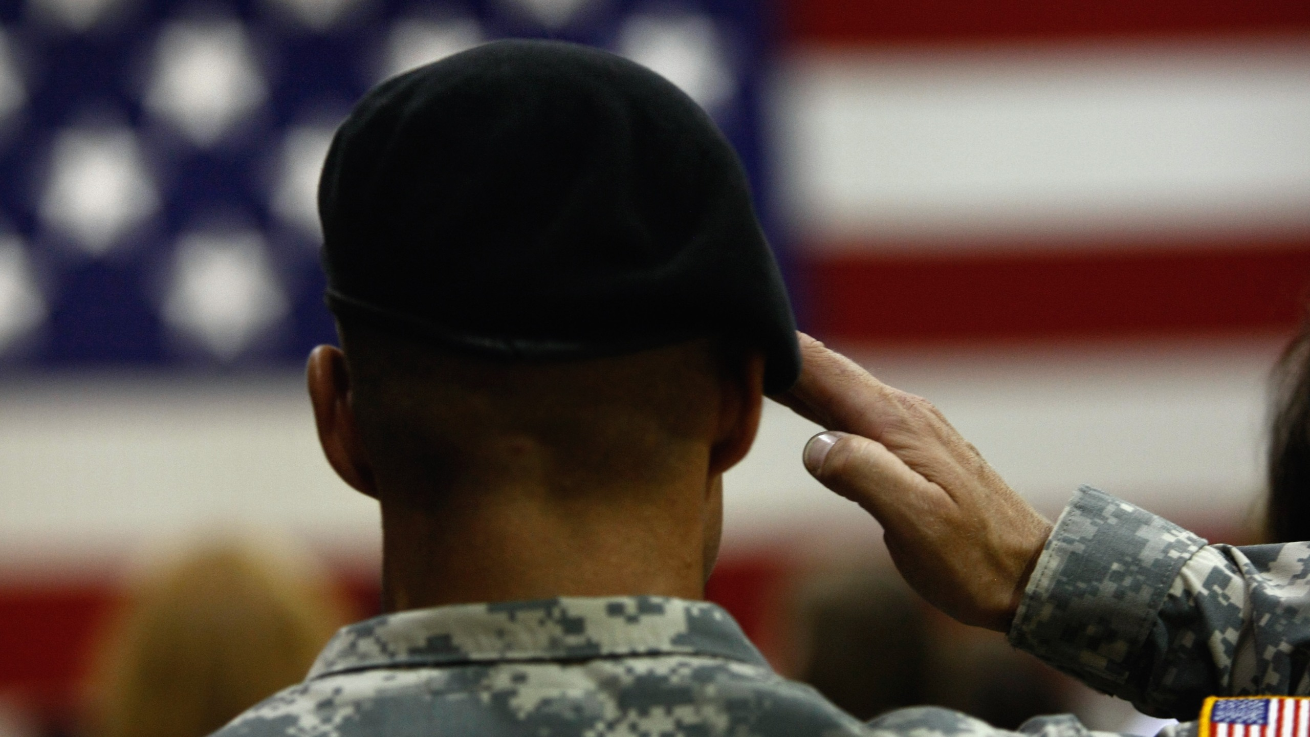 A U.S. Army soldier salutes during the national anthem as soldiers return home from Iraq on August 29, 2009 in Fort Carson, Colorado. (Credit: John Moore/Getty Images)