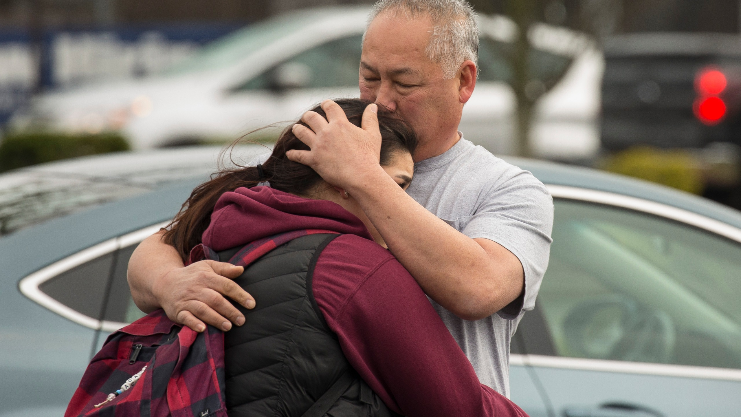 Kaihei Kim (right) comforts his daughter, Acacia Kim, 18, (left), a high school student that takes classes at Highline College, after a threat of an active shooter shut down campus at Highline College on Feb. 16, 2018, in Des Moines, Wash. Police found no evidence of a shooting despite students reporting that they heard gunfire. (Credit: David Ryder/Getty Images)