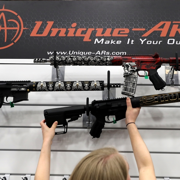 """A vendor hangs an AR-15 rifle with a custom """"Trump - Make America Great Again"""" hand guard at the Unique ARs booth during the NRA Annual Meeting & Exhibits at the Kay Bailey Hutchison Convention Center on May 5, 2018 in Dallas, Texas. (Credit: Justin Sullivan/Getty Images)"""