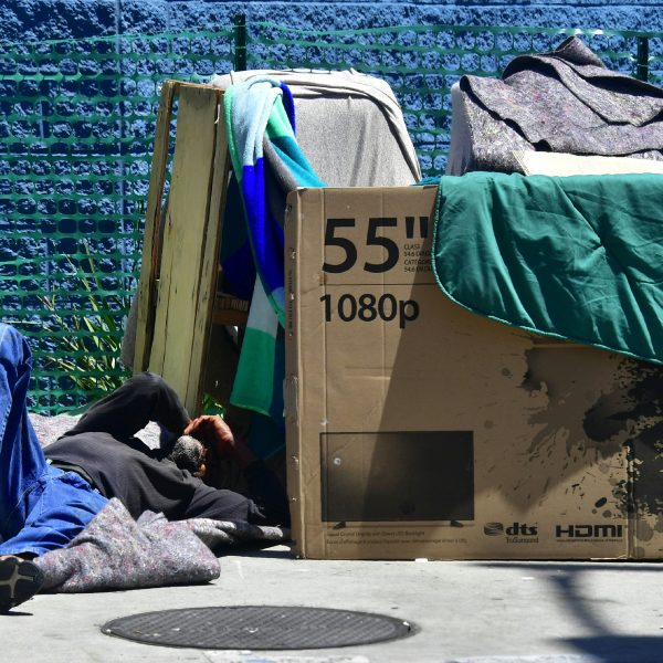 A homeless man sleeps beside his makeshift temporary shelter on a street in downtown Los Angeles on June 25, 2018. (Credit: Frederic J. Brown / AFP / Getty Images)