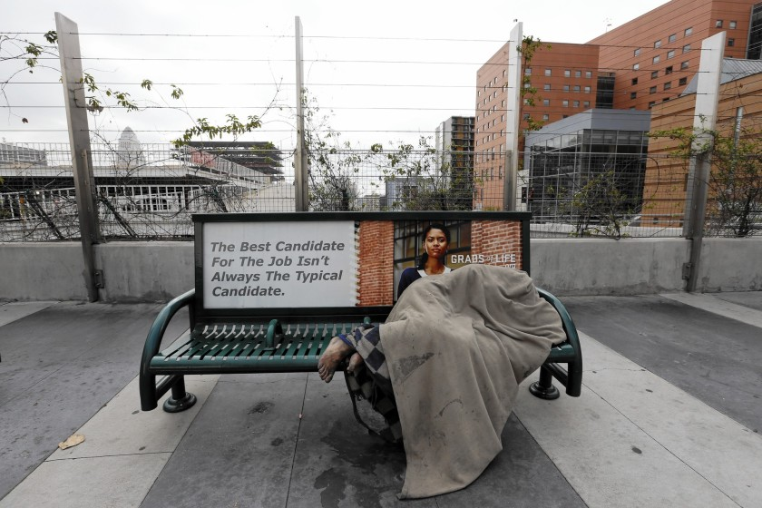 A homeless person sleeps beneath a blanket on a bus bench on South Grand Avenue in Los Angeles in this undated photo. (Credit: Francine Orr / Los Angeles Times)