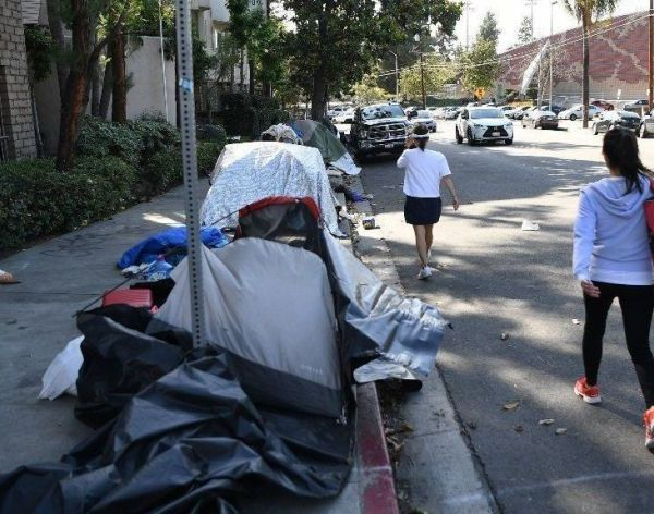 Pedestrians walk in the street instead of on the sidewalk, where homeless people have set up tents outside the Villa Adobe apartment building in Koreatown in this undated photo. (Credit: Wally Skalij / Los Angeles Times)
