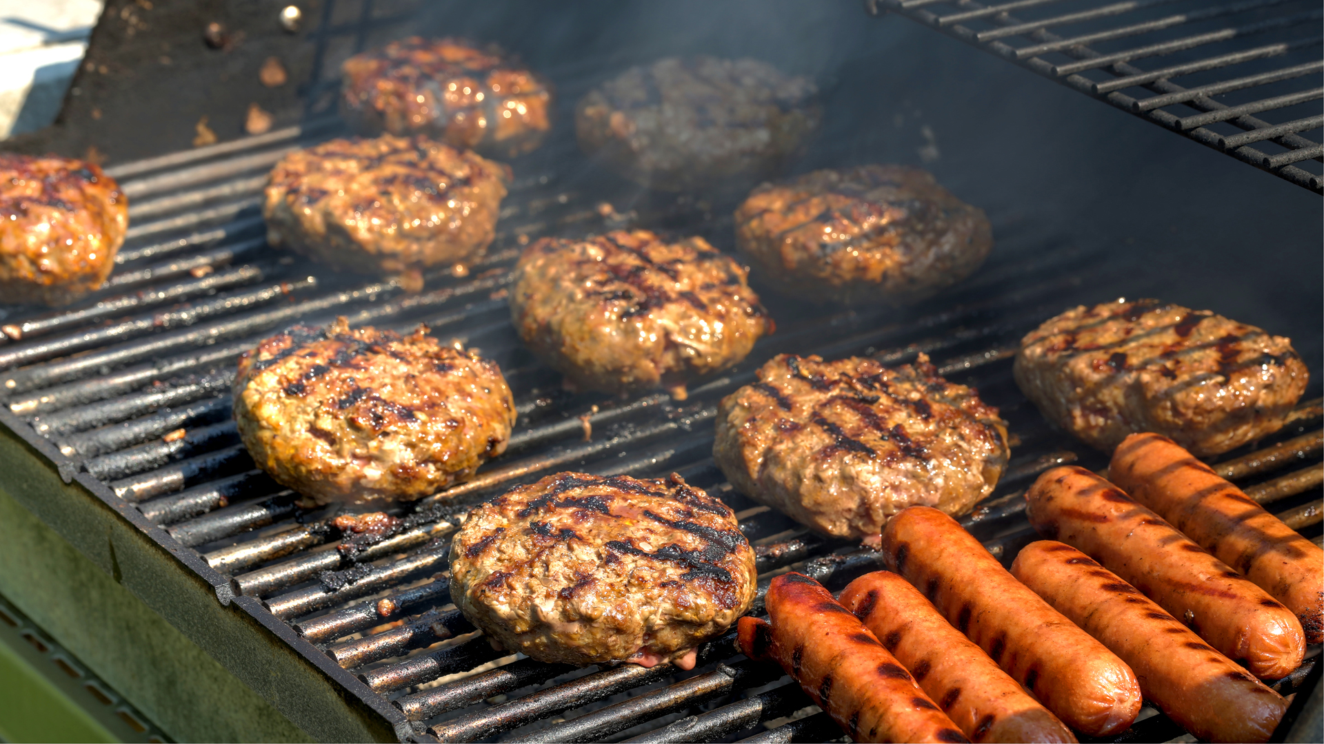 Hamburgers and hot dogs on a grill are seen in this file photo. (Credit: iStock/Getty Images Plus)