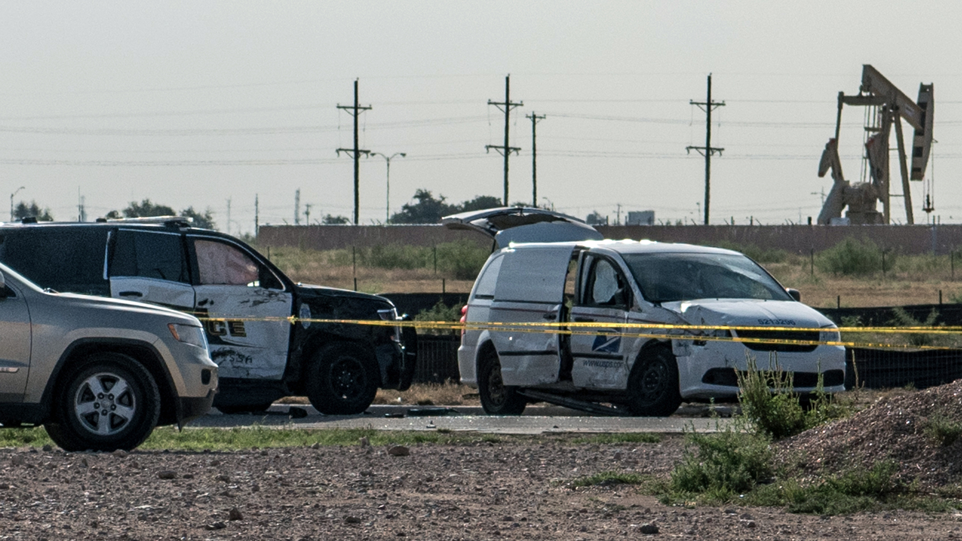 A damaged police vehicle and U.S. Postal Service van blocked off with tape nearby to where a gunman was shot and killed at Cinergy Odessa movie theater following a deadly shooting spree on September 1, 2019 in Odessa, Texas. (Credit: Cengiz Yar/Getty Images)