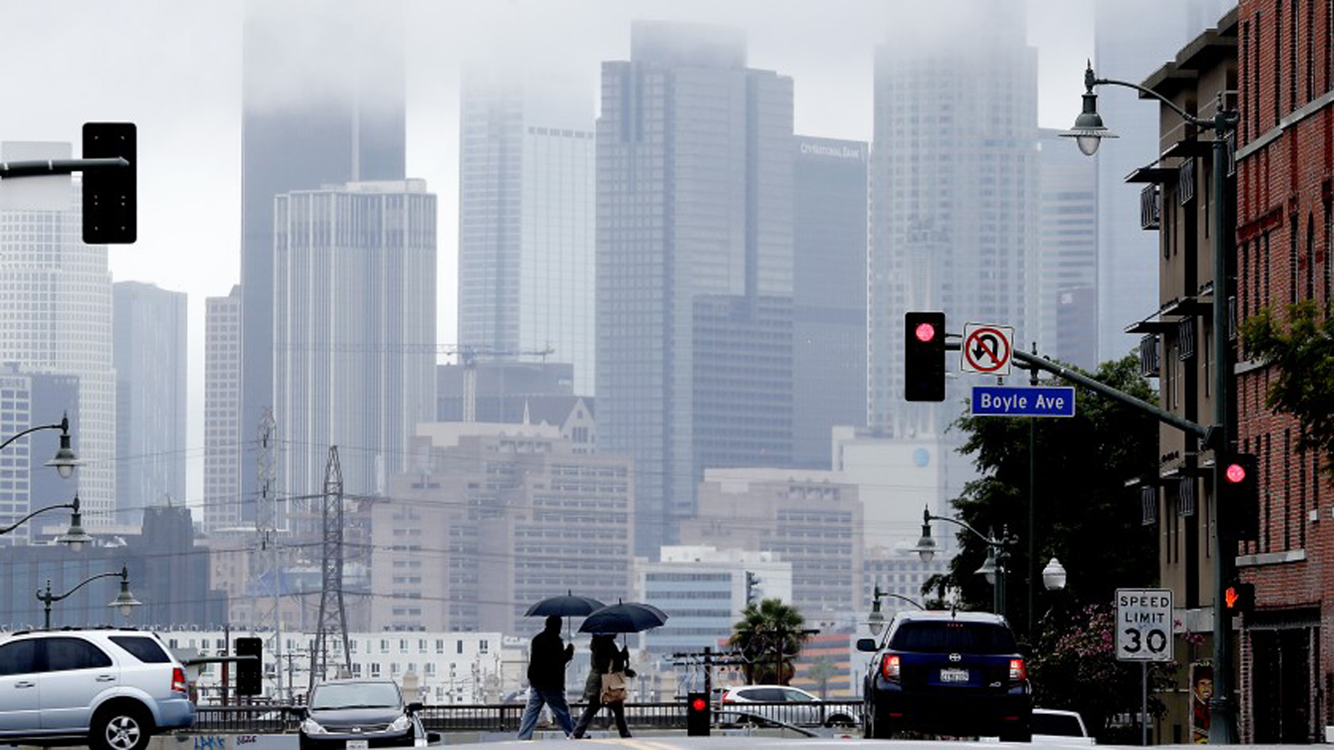 Pedestrians cross First Street in Boyle Heights as clouds partially obscure the downtown L.A. skyline on March 6. The first rain of fall made for a drizzly morning Sept. 26 in Los Angeles.(Credit: Luis Sinco / Los Angeles Times)