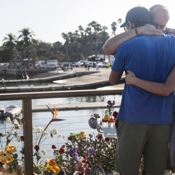 People embrace at Santa Barbara Harbor at a makeshift memorial for victims of the Conception boat fire on Sept. 3, 2019 in Santa Barbara. (Credit: Mario Tama/Getty Images)