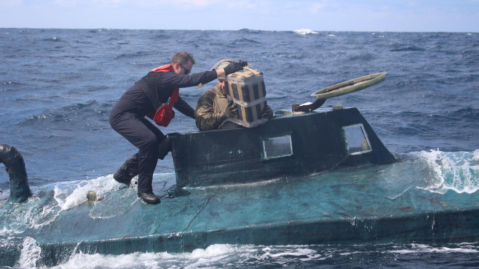 "Coast Guard boarding team members climb aboard the 40-foot ""narco sub."" (Credit: U.S. Coast Guard District)"