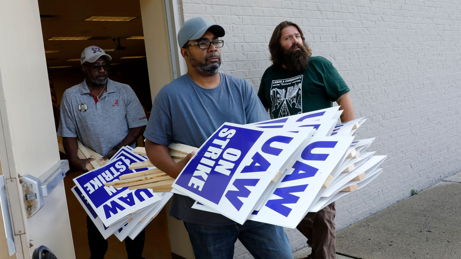 General Motors Co. employee Carl Ellison carries strike signs outside of the United Auto Workers (UAW) Local 163 which represents GMs Romulus Powertrain on September 15, 2019 in Westland, Michigan. (Credit: Jeff Kowalsky/AFP/Getty Images)