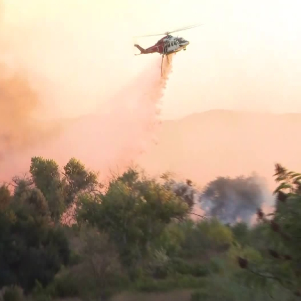 A helicopter drops water on the Sepulveda Fire in the Sepulveda Basin on Oct. 24, 2019. (Credit: KTLA)