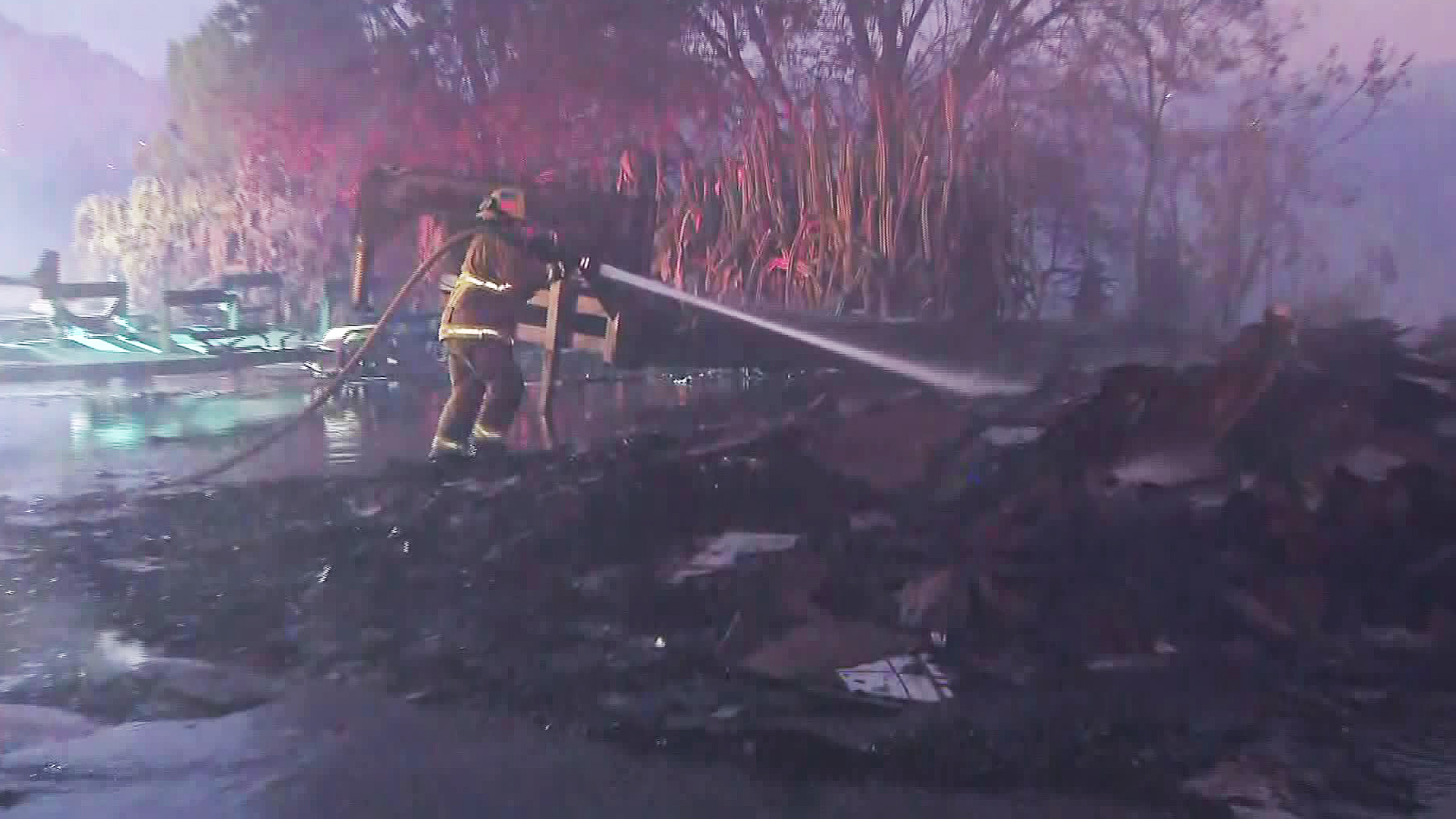 A firefighter battling the 46 Fire douses some burning material on Oct. 31, 2019. (Credit: KTLA)