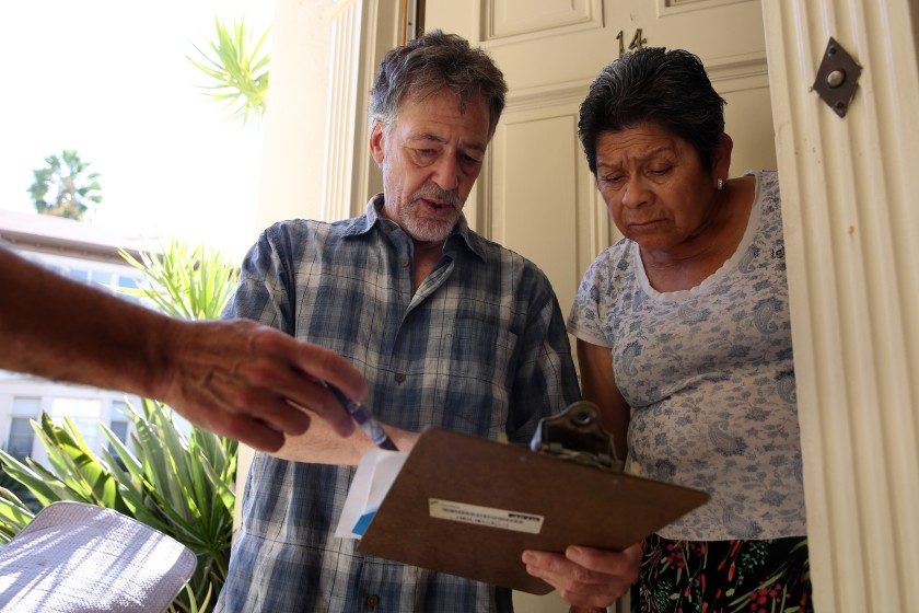 Jon Hofferman talks to fellow tenant Felicita Fuentes, right, with tenant Darrin Wilstead holding a pen at left, about their concerns with a proposed agreement with the owner of their apartment complex in Hollywood in October 2019. (Credit: Dania Maxwell / Los Angeles Times)
