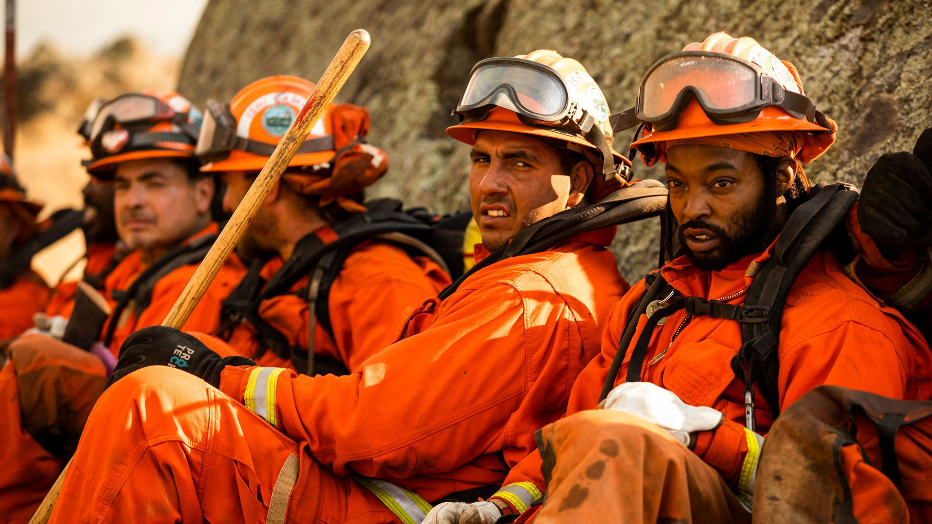 A crew of inmate firefighters takes a break from battling the Kincade Fire in Healdsburg. (Credit: Philip Pacheco/AFP/Getty Images)