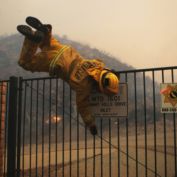 A Cal Fire firefighter hops over a locked gate while working the Tick Fire on October 24, 2019 in Canyon Country. (Credit: Mario Tama/Getty Images)
