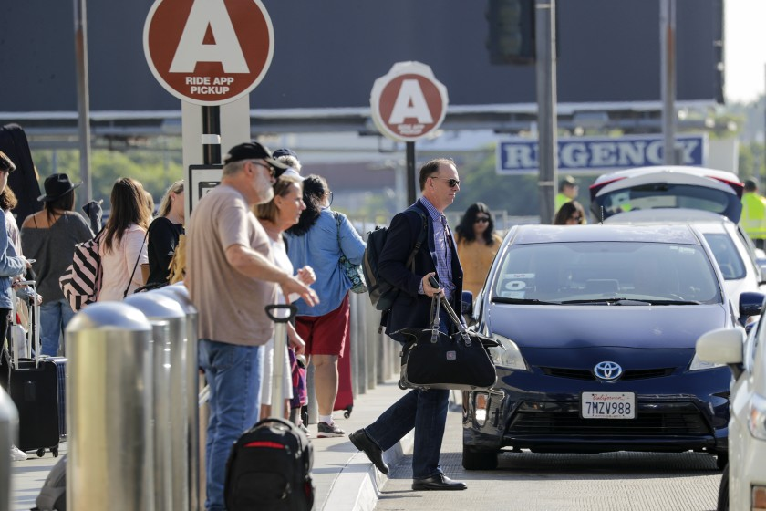 Travelers wait for Uber and Lyft cars at Los Angeles International Airport. (Credit: Irfan Khan / Los Angeles Times)